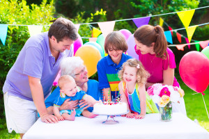 Happy big family - young parents grandmother and three kids teenage boy toddler girl and little baby celebrating birthday party with cake and candles in the garden decorated with balloons and banners