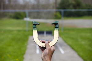 Player lines up to pitch a horseshoe in an outdoor court hand and horseshoe in focus