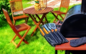 Summer Party or Picnic Scene. BBQ Grill with BBQ tools garden furniture on the lawn in blurred background.